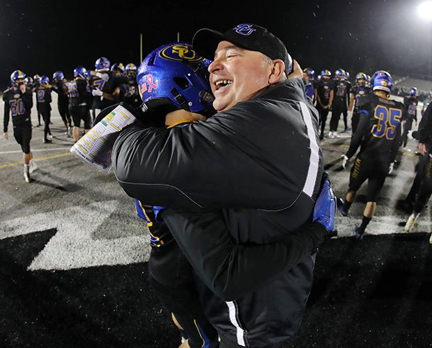 Sutter head coach Ryan Reynolds hugs one of his players after winning Saturday's Northern Section Division III title game.