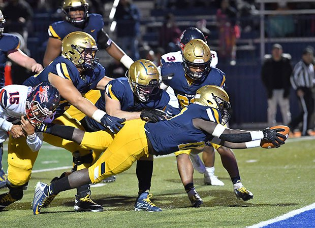 Running back Travis Dixon drives into the end zone for an Aquinas touchdown.