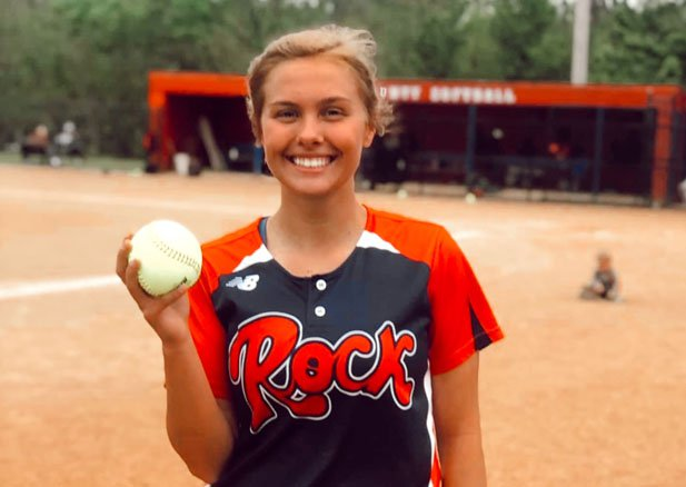 Rockcastle senior pitcher Madison McIntosh holds up the ball used to record her 21st and final strikeout in Tuesday's perfect game vs. Lincoln County.