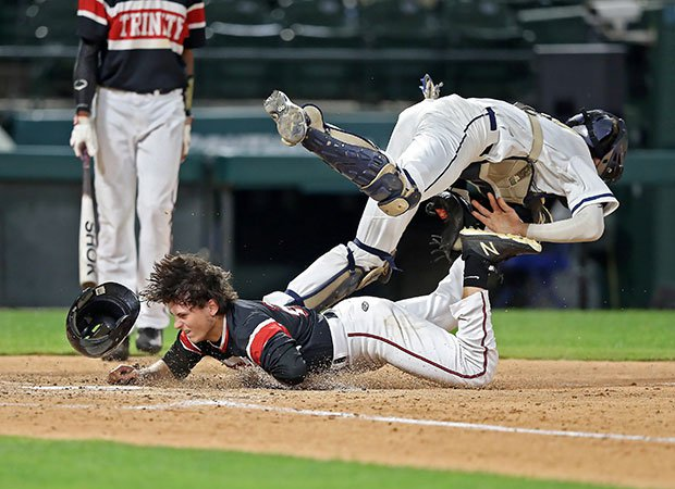 A Trinity (Texas) base runner is called out after colliding with a Flower Mound catcher in a UIL 6A playoff game at Globe Life Park, home of the Texas Rangers.