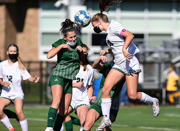 Yorktown (N.Y.) midfielder Chayce Buono (right) attempts to head a shot on goal as she's challenged by a Brewster defender.
