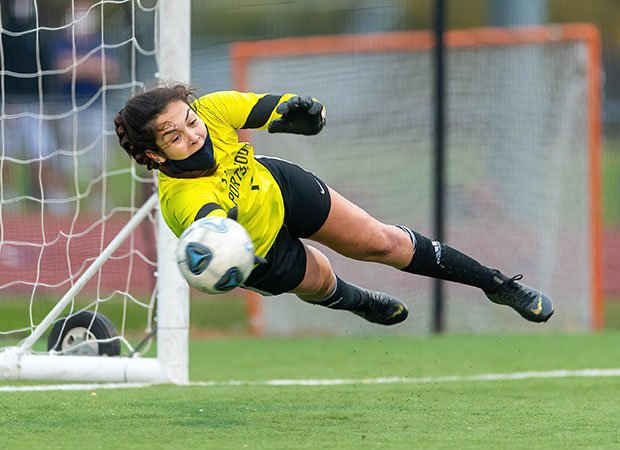 Goalie (N.H.) Sophia Rinalli of Portsmouth makes a diving save in a game against Exeter.