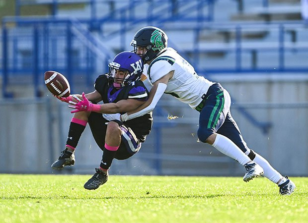 Arvada West (Colo.) cornerback AJ St. James looks for an interception in front of intended receiver Sam Jacobs of ThunderRidge.