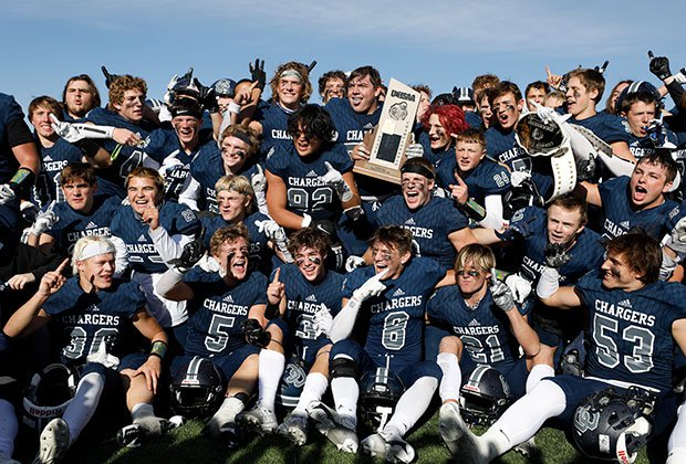 Corner Canyon players proudly display the trophy while celebrating their victory in the 6A state championship game.