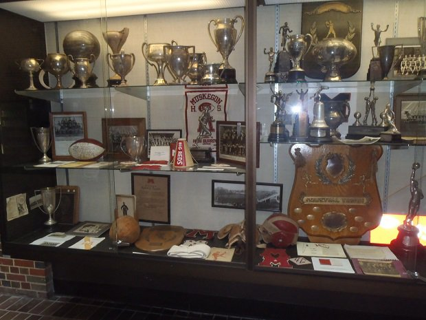 The trophy case at Muskegon is filled with accomplishments from the Big Reds, who have won more football games than any school in Michigan.
