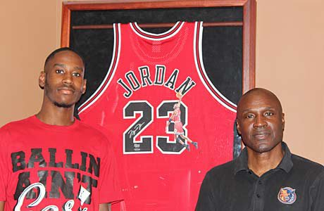 Justin Jordan and his father Larry pose in front of Michael's famous No. 23.