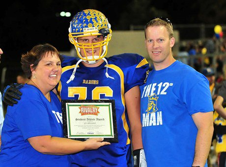 J.D. Hinnant stands with his parents, Blake and Laurie, before an October game against Edison.