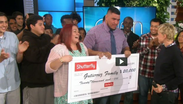 """Hawthorne assistant football coach Sione Gutierrez and wife Vanessa Williams receive a check for $20,000 from Shutterfly on Monday's taping of the """"Ellen"""" show. Hawthorne team members cheer on."""