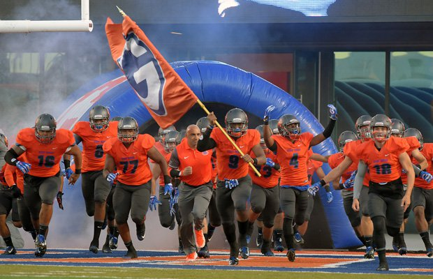 Bishop Gorman head coach Kenny Sanchez and his players rush onto the field for their home opener Friday night.