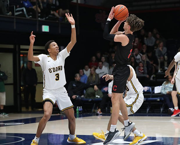 Campolindo point-guard Aidan Mahaney takes a jump shot in front of Monty Bowser of Bishop O'Dowd.