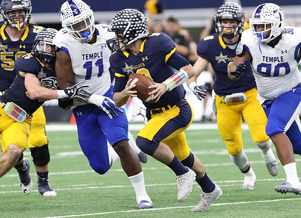 Highland Park quarterback John Stephen Jones attempts to elude two Temple defenders.
