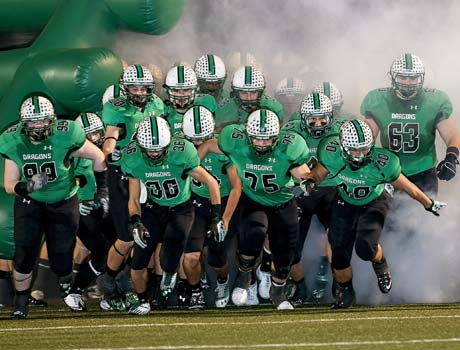 Carroll players rush onto the field during pregame introductions Saturday night.