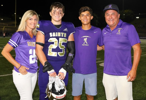 Connor Heffler – pictured with his family after a Sept. 6 win over Loyola – raised more money to fight childhood cancer than any other high school football player in the country.
