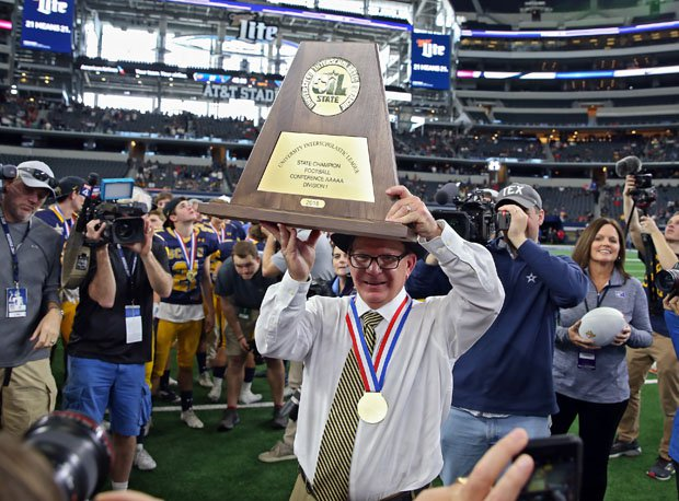 Highland Park coach Randy Allen holds up the program's sixth state championship trophy.