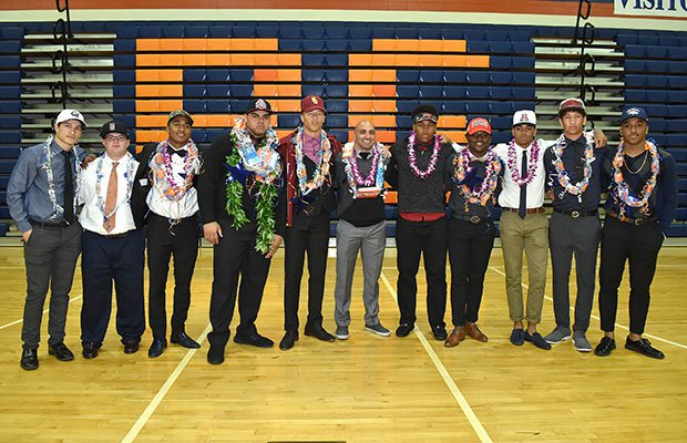 The Bishop Gorman football team and coach Kenny Sanchez pose following a ceremony at school.