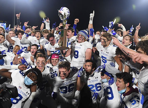 St. Xavier players proudly display the championship trophy.