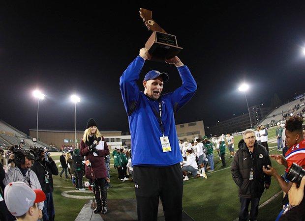 Folsom coach Kris Richardson proudly hoist the state championship trophy.