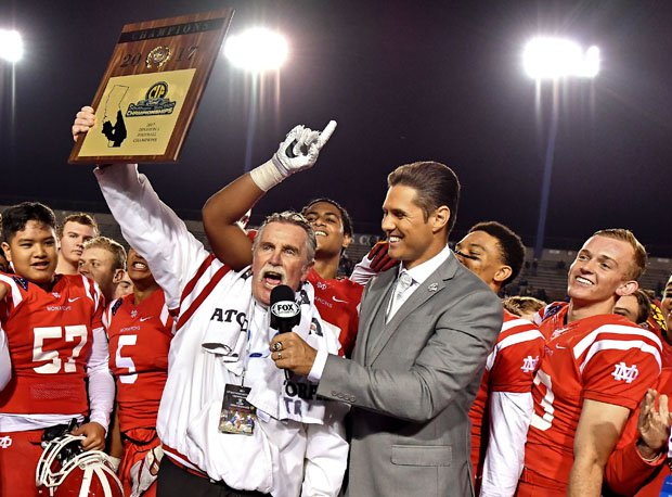 Mater Dei coach Bruce Rollinson holds up hardware after the Monarchs won their first Southern Section crown since 1999.