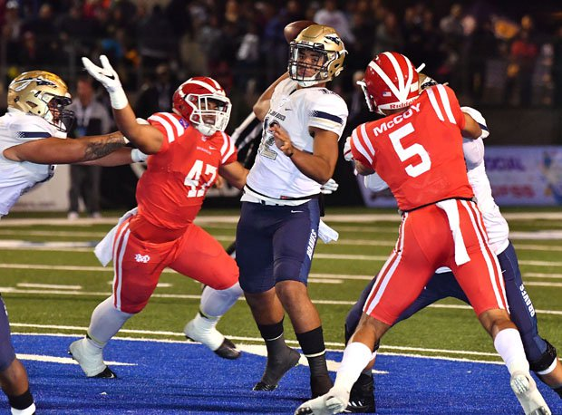 St. John Bosco sophomore quarterback DJ Uiagalelei is pressured by Kyron Ware-Hudson (42) and Bru McCoy (5).