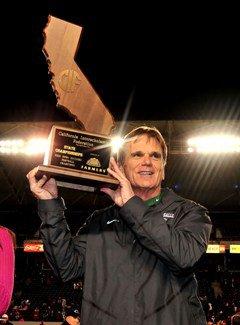 De La Salle coach Bob Ladouceur proudly displays the championship trophy.