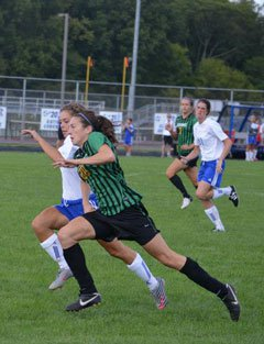 Agnew (in green and black) fights to getaway in a high school match.