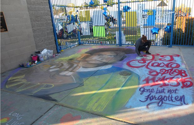 A woman paints a chalk mural on the ground inside the football stadium in tribute to JJ Clavo.