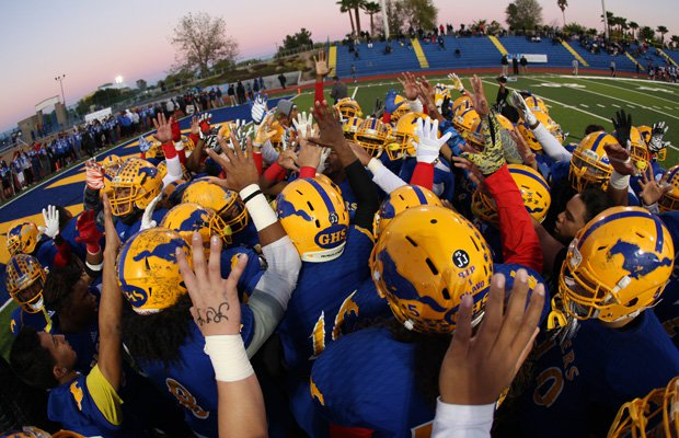 Grant players raise five fingers in a pregame tribute to Jaulon Clavo, who wore jersey number 5.