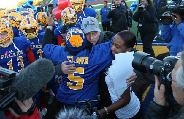 Grant head coach Mike Alberghini embraces Nicole Clavo at midfield before the start of Monday's playoff game.