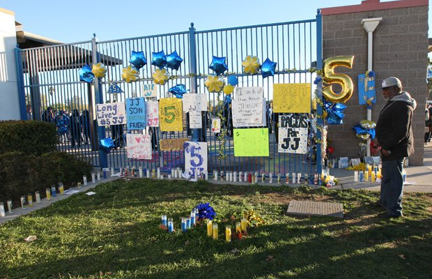 A man looks at a memorial set up for Jaulon Clavo outside the home entrance to the Grant football stadium.