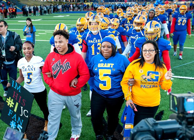 Nicole Clavo (second from the right), the mother of Jaulon, leads the Grant players onto the field before kickoff. Grant senior Malik Johnson (third from the right) joins her as he was shot in the arm in the shooting that claimed Nicole's son.