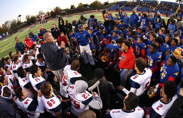 Players and coaches from Grant and Beyer high schools gather at midfield to pray in honor of slain football player Jaulon Clavo before the start of their playoff game Monday night.
