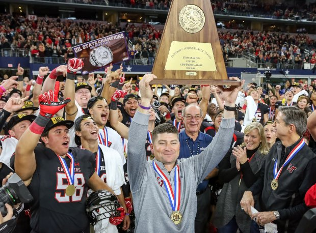 Lake Travis head coach Hank Carter celebrates with his team after beating The Woodlands in last season's state title game.