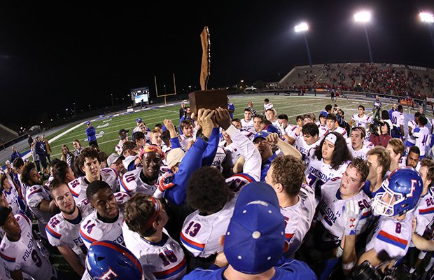 Folsom coaches and players hoist the championship trophy following their thrilling victory in overtime.