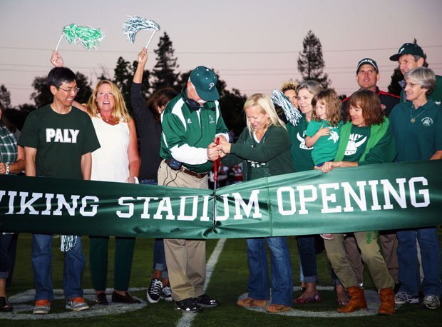 Palo Alto coach Earl Hansen cuts the ribbon, commemorating the opening of school's renovated stadium Friday. See San Francisco 49ers' coach Jim Harbaugh in the background.