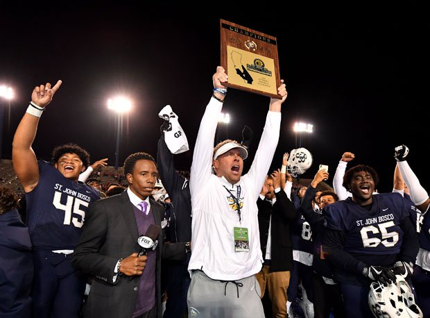 Bosco coach Jason Negro holds Southern Section Division 1 trophy up high.