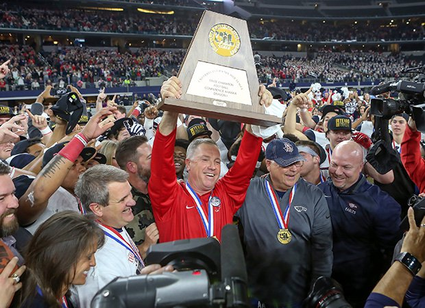 Head coach Terry Gambill proudly hoists the trophy following his team's victory in the UIL 6A Division 1 championship game at the end of last season.