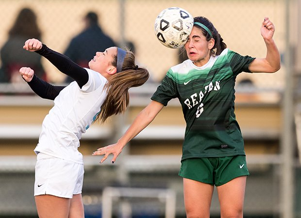 A Johnson (San Antonio) player hits a header behind a Reagan (San Antonio) player during a game in Texas.
