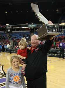 Gary McKnight holds up record ninth state title trophy.