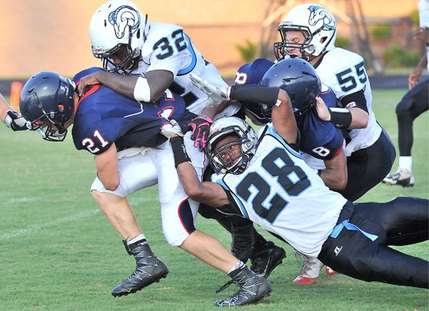 Apex Friendship (N.C.) running back Jacob Kelley drags several Cleveland (N.C.) defenders.