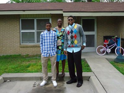 Malik (left) and his brother Marcus pose with their mother Jackie on Easter 2011 in front of their former home in Lepanto.