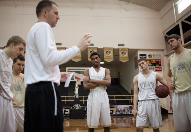 Malik (center) and his teammates listen to head coach Jason McMahan during a recent practice. McMahan has been the man at the helm leading the school's resurgence.