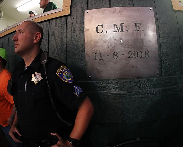 Paradise Police Sgt. John Alvies looks on during the varsity game while standing next to the newly installed plaque marking the date the fire struck. His son, Josh, is a member of the team.