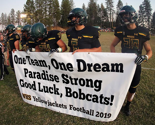 Paradise captains hold a banner presented to them by Williams players before the coin toss.