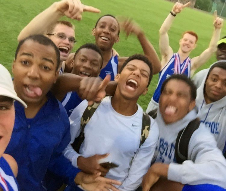 Imoter Mngerem (tongue out) is mobbed by teammates during track and field practice at Riverside Military Academy.