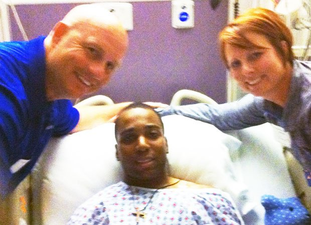 Coach Kelly Davis (left) and his wife Lisa Davis (right) flank Imoter Mngerem at hospital.