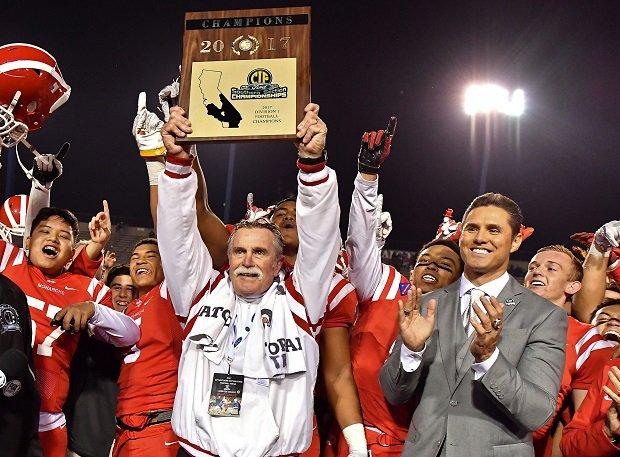 Mater Dei coach Bruce Rollinson raises the CIF Southern Section title plaque.