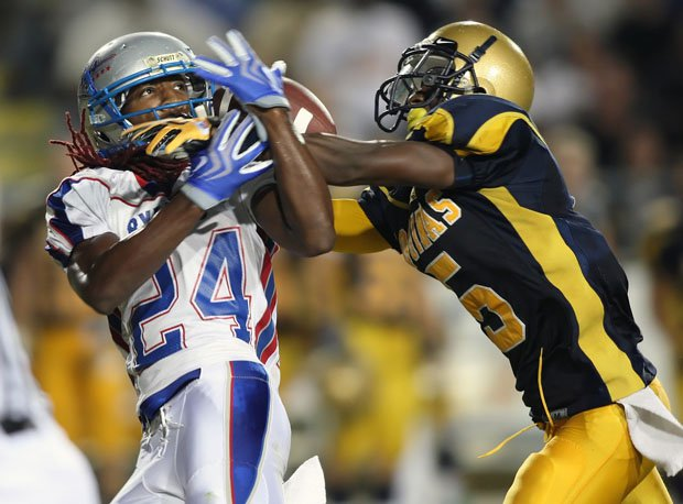 Byrnes wide receiver Isaiah King tries to haul in a pass under heavy duress from Keione Payne of St. Thomas Aquinas.