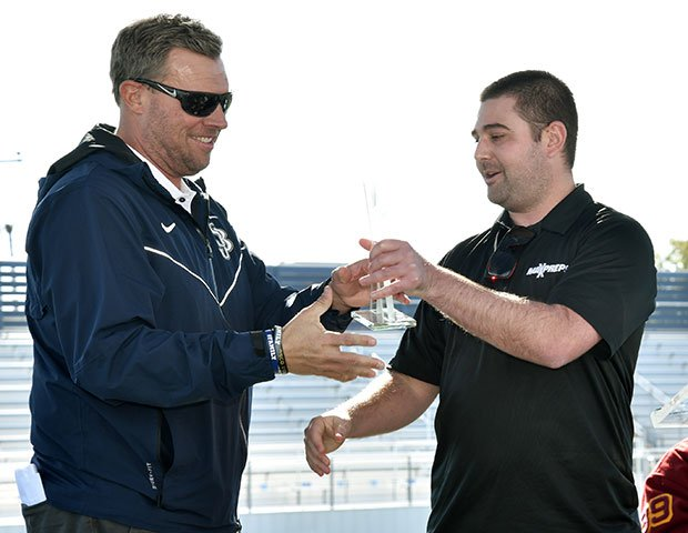 MaxPreps National Football Editor Zack Poff (right) presents the national champions trophy to head coach Jason Negro during a ceremony Friday.