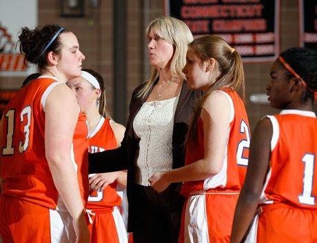 Veteran Danbury girls basketball coach Jackie DiNardo (center) huddles with her team during Thursday night's game.