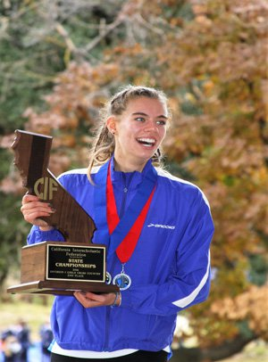 O'Keeffe holding Davis' second-place trophy at the state cross country meet in Fresno.